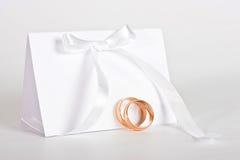 Hochzeitsringe und höfliche Karte Stockbild