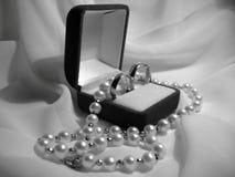 Hochzeitsringe und Perlenhalskette Stockfotos