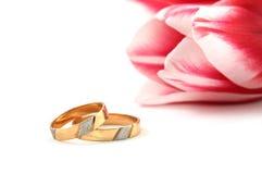 Hochzeitsringe und rosafarbene Tulpe Stockfoto