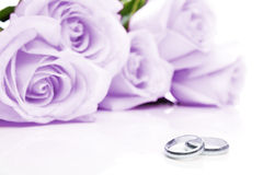 Hochzeitsringe und -rosen Stockfotografie