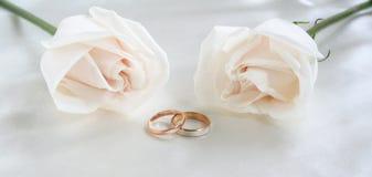Hochzeitsringe und -rosen als Hintergrund Lizenzfreie Stockbilder