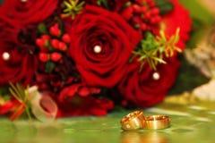 Hochzeitsringe und rote Rosen Stockbilder