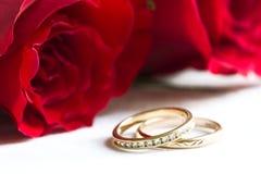 Hochzeitsringe und rote Rosen Stockfotos
