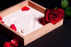 Hochzeitsringe und rote Rosen Lizenzfreie Stockbilder