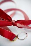 Hochzeitsringe und rotes Farbband Stockfotografie