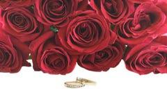 Hochzeitsringe vor einem Blumenstrauß der roten Rosen. Lizenzfreie Stockbilder