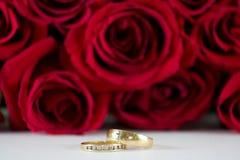 Hochzeitsringe vor roten Rosen. Stockfotografie