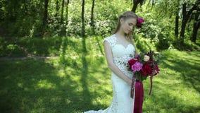 Hochzeitsschleppkleid Schöner Hochzeitsblumenstrauß von Blumen in den Händen der jungen Braut hochzeiten junge Frau im Park, Wald stock video footage
