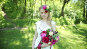 Hochzeitsschleppkleid Schöner Hochzeitsblumenstrauß von Blumen in den Händen der jungen Braut hochzeiten junge Frau im Park, Wald stock video