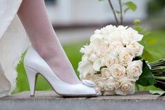 Hochzeitsschuh und Brautblumenstrauß Weibliche Füße in den weißen Hochzeitsschuhen und -blumenstrauß Stockfotos