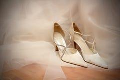 Hochzeitsschuhe auf weißem Brautkleid. Lizenzfreies Stockfoto