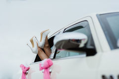 Hochzeitsschuhe der Füße der Braut weiße im Autofenster stockfoto