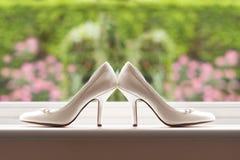 Hochzeitsschuhe durch ein Fenster Stockfotografie