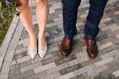Hochzeitsschuhe, Füße Mann und Frau auf der Steinstraße lizenzfreie stockbilder