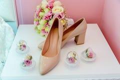 Hochzeitsschuhe mit Blumenstrauß lizenzfreie stockbilder