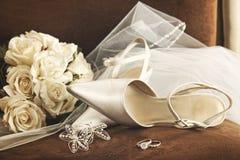 Hochzeitsschuhe mit Blumenstrauß der weißen Rosen und des Ringes Lizenzfreies Stockfoto