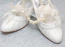 Hochzeitsschuhe mit Perlenhalskette Stockfoto