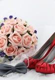 Hochzeitsschuhe und ein Blumenstrauß von Blumen Lizenzfreie Stockbilder