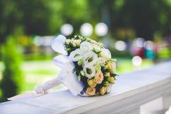 Hochzeitssommerblumenstrauß auf hölzernem weißem Geländer, auf einem grünen Hintergrund Lizenzfreies Stockfoto