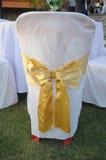 Hochzeitsstühle in der Reihe verziert mit goldenem Farbband Stockfotos