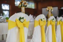 Hochzeitsstühle verziert in einer Banketthalle Stockbild