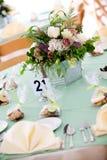 Hochzeitstabelle mit Blumenmittelstück Stockbilder