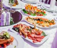 Hochzeitstafel gedient mit geschmackvollen Mahlzeiten, kaltes Fleisch der Antipastoservierplatte, Fischservierplatte, Käseservier stockfotos