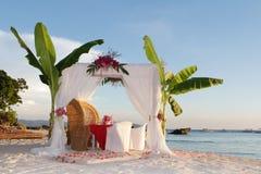 Hochzeitstafel und Einrichtung mit Blumen auf Strand Lizenzfreies Stockfoto
