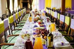 Hochzeitstafel und Stühle mit fioletovaya und gelben Bändern Stockfoto