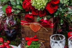 Hochzeitstafeldekor: blüht Zusammensetzung mit den Rosen, Beeren, Kräutern und Grün, die in der Holzkiste stehen Brautdetails und Lizenzfreies Stockfoto