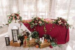Hochzeitstafeldekoration mit den roten und rosa Blumen auf dem roten Stoff Lizenzfreie Stockbilder