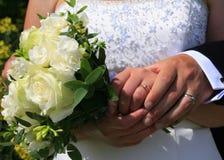 Hochzeitstag übergibt Ringe und Blumenstrauß Stockfoto