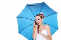 Hochzeitstag. Braut mit dem Unterhaltungstelefon des blauen Regenschirmes lokalisiert Stockfoto