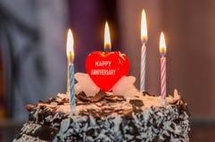 Hochzeitstag mit einem schönen Herzen feiernd, formen Sie Kerze auf Kuchen Stockfotografie