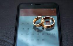 Hochzeitstermin mit Ringen am Telefon Stockfoto