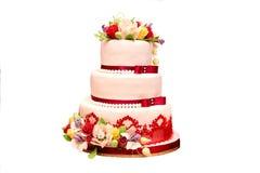 Hochzeitstorte in der weiß-roten Farbe mit Blumen lizenzfreie stockfotografie