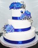 Hochzeitstorte mit blauen Bändern und Blumen Stockbilder