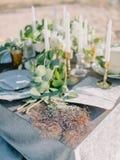 Hochzeitstorte mit Dekorationen und Eukalyptusblättern Fokus auf den Gläsern lizenzfreie stockfotografie