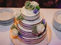 Hochzeitstorte mit den Reihen verziert mit Blumen Stockfotos
