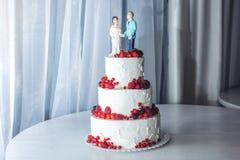 Hochzeitstorte mit Figürchen der Braut und des Bräutigams auf Oberseite verziert mit Erdbeeren auf den Reihen Lizenzfreie Stockbilder
