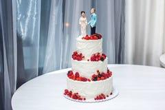 Hochzeitstorte mit Figürchen der Braut und des Bräutigams auf Oberseite verziert mit Erdbeeren auf den Reihen Stockfotos
