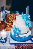 Hochzeitstorte mit gelbem beige rotem Blau der Blumen lizenzfreie stockfotos