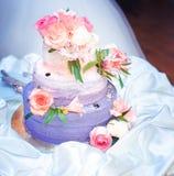 Hochzeitstorte mit Rüschen und Rosen in der rosa-violetten Farbe Lizenzfreies Stockfoto