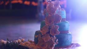 Hochzeitstorte steht auf der Tabelle, die durch Blumen umgeben wird stock video footage