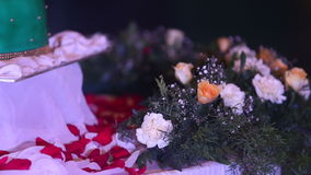 Hochzeitstorte steht auf der Tabelle, die durch Blumen umgeben wird stock footage