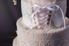 Hochzeitstorte wie Kleid mit Band im Korsett mit Rosen stockbilder