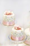 Hochzeitstorten in Sahne- und in rosa mit Perlen. Stockbild