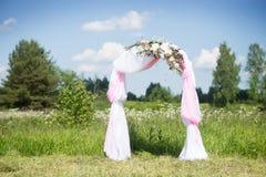 Hochzeitstraditionsbogen mit Blumendekor auf Hintergrund des blauen Himmels Lizenzfreies Stockfoto