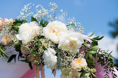 Hochzeitstraditionsbogen mit Blumendekor auf Hintergrund des blauen Himmels Lizenzfreie Stockfotografie