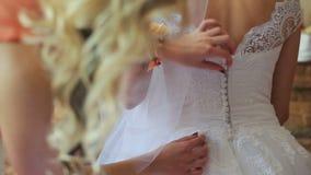 Hochzeitsvorbereitung, Hochzeitskleid, das oben von der Brautjungfer gebunden wird stock footage